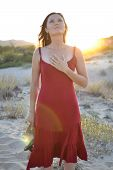 stock photo of gratitude  - Beautiful young woman holding her hands on her heart - JPG