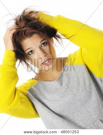 A beautiful teen girl in sloppy sweats pulling her hair in exasperation.  On a white background.