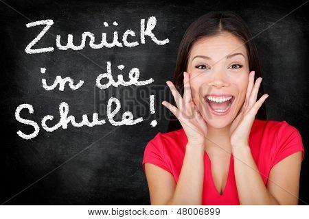 Zuruck in die Schule - German student screaming happy Back to School written in German on blackboard by female teacher. Smiling happy woman teaching German language or university student in college