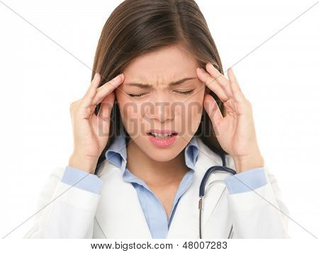 Doctor with headache stressed. Nurse / doctor with migraine headache overworked and stressed. Health care professional in lab coat wearing stethoscope isolated on white background.