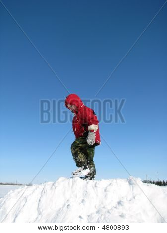 Boy Plays On Snowy Hill