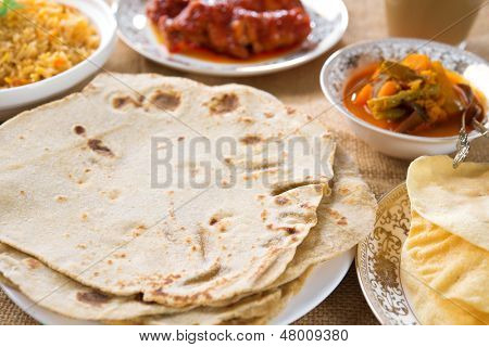 Chapatti roti or chapati, curry chicken, biryani rice, salad, masala milk tea and papadom. Indian food on dining table.