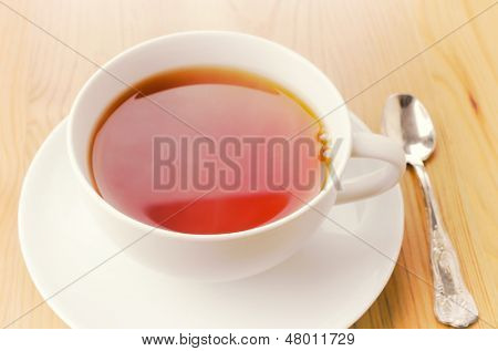 Cup of tea on wooden background, morning light