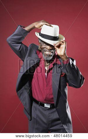 Alegre homem sênior em terno ajustando fedora contra o fundo vermelho