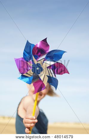Blurred girl with closeup of pinwheel in her hand on beach