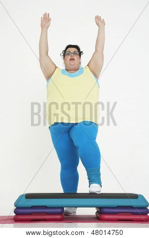 Full length of a plus size woman on exercise steps raising hands against white background