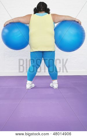 Rear view of an overweight woman holding two exercise balls in healthclub