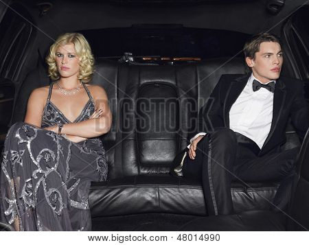 Angry young couple in limousine after breaking up