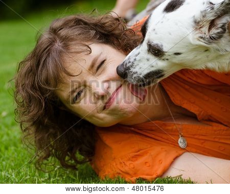 Woman making disgusted face while being licked by her pet dog