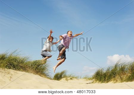 Cheerful father and son holding hands and jumping on sand at beach