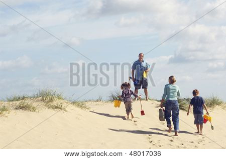 Rear view of family walking up sand dune on beach against the sky