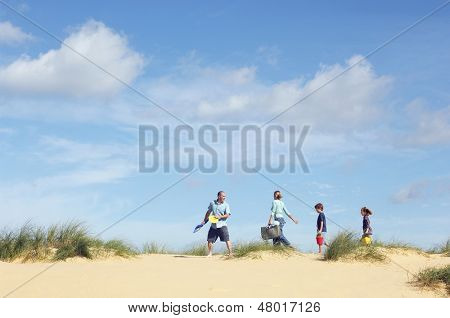 Side view of family walking sand dune on beach against the sky