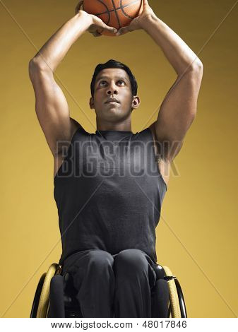 Paraplegic athlete sitting in wheelchair and shooting basketball against yellow background
