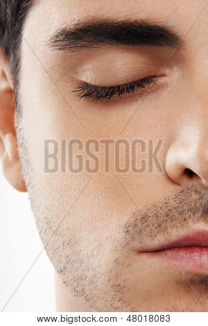 Closeup of young man meditating with eyes closed on white background