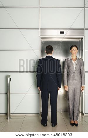 Businessman and businesswoman standing in front of elevator in office