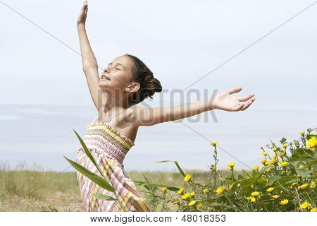 Preadolescent girl with arms outstretched enjoying sunlight while standing by flower in field