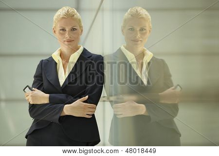 Portrait of confident young businesswoman leaning against glass partition in office