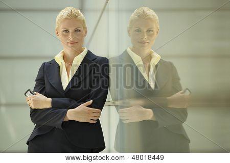 Retrato de confianza empresaria joven apoyado contra la partición de cristal en la oficina
