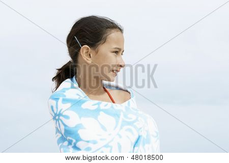 Happy little preadolescent girl wrapped in towel looking away while standing at beach