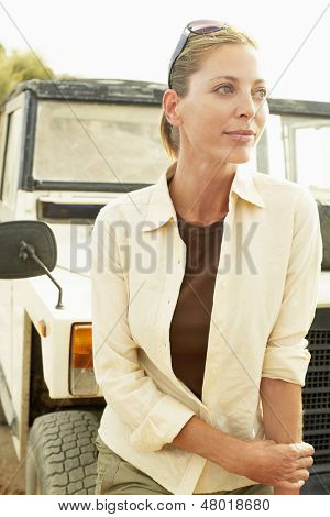 Thoughtful middle aged woman standing in front of four-wheel-drive car