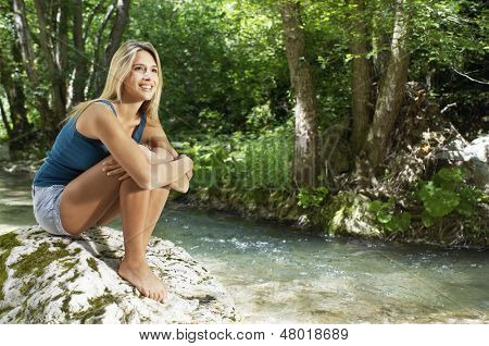 Thoughtful young woman hugging knees while looking away by forest river