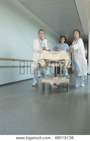 Physicians rushing patient on gurney down hospital corridor