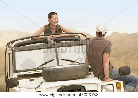 Young couple in stationary four-wheel-drive vehicle in desert