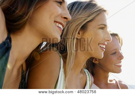 Closeup of happy female friends smiling while looking away