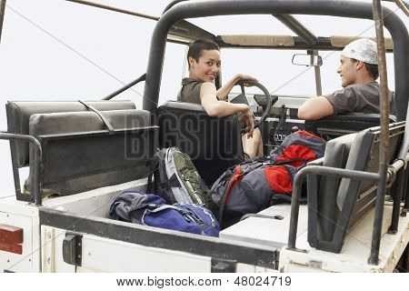 Happy young couple in four-wheel-drive vehicle outdoors
