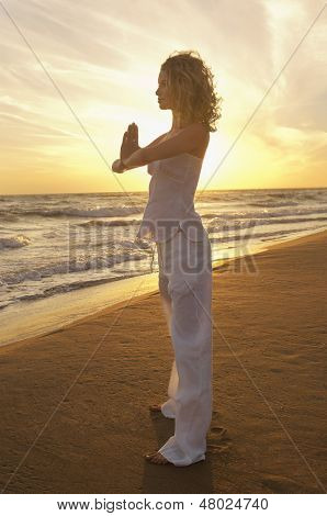Full length of young woman with hands clasped practicing yoga while standing on sand at beach