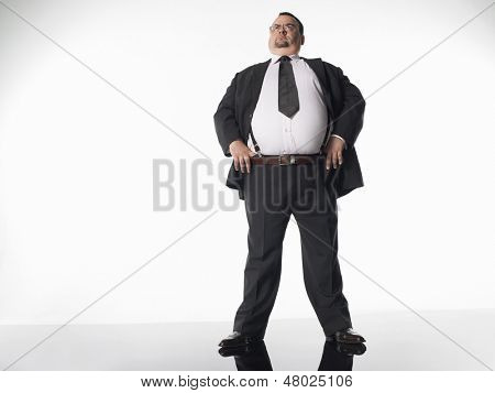 Full length of an overweight businessman standing with hands on hips against white background