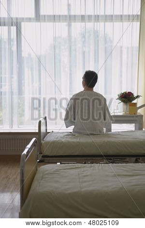 Rear view of a male patient sitting in hospital bed