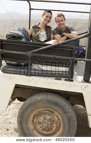 Portrait of happy young couple in stationary four-wheel-drive vehicle in desert
