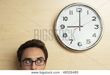 Headshot of young businessman wearing spectacles looking at clock on wooden wall in office