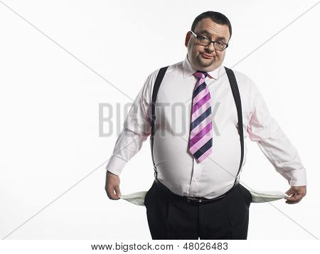 Portrait of an overweight businessman pulling out empty pockets against white background