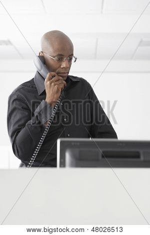 Serious African American businessman using telephone at computer desk