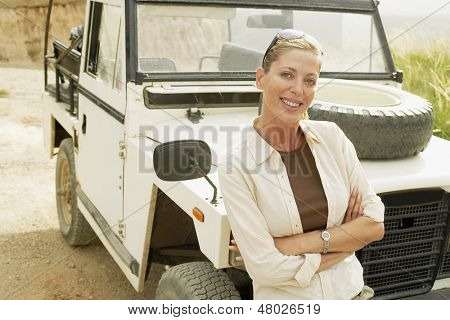 Portrait of happy woman standing in front of four-wheel-drive car in desert