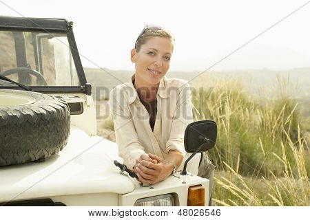 Portrait of happy middle aged woman standing by four-wheel-drive car outdoors