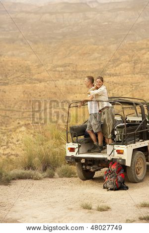 Middle aged couple standing in back of four-wheel-drive car on cliff edge in desert