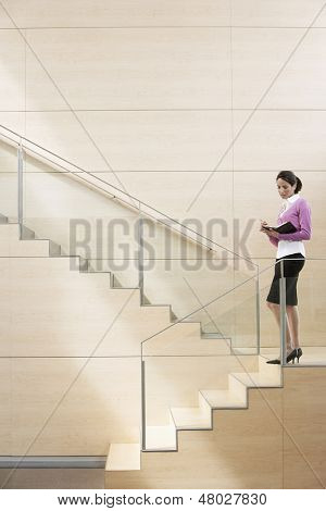 Young businesswoman writing in diary while standing by glass railing on steps in office