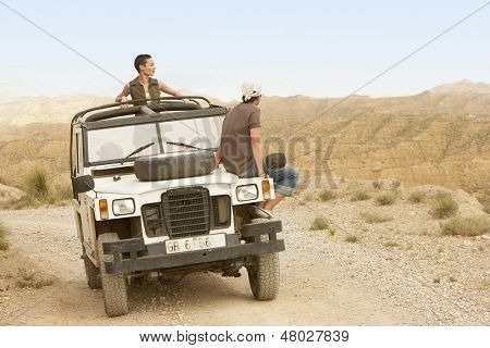 Young couple in four-wheel-drive looking at mountain range