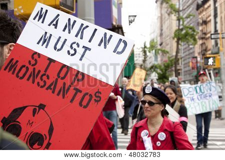 NEW YORK-MAY 25: A protestor on Broadway holds a sign that says 'Mankind Must Stop Monsanto' at the March Against Monsanto from Union Square in the movement against GMO's on May 25, 2013 in New York.