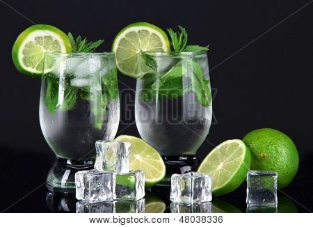 Glasses of cocktail with ice on black background