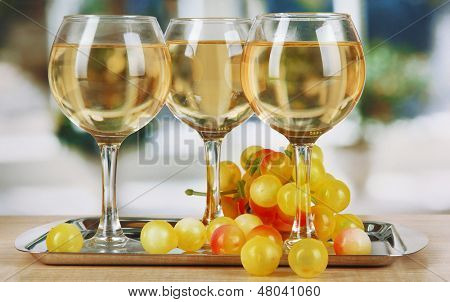 White wine in glass on salver on window background