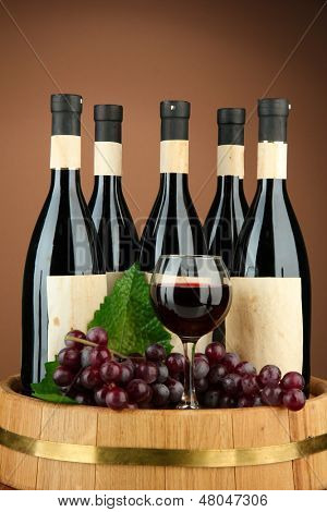 Composition of wine bottles, glasses and  grape,on wooden barrel, on brown background