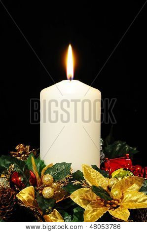 White candle and Christmas flowers.