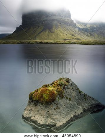 Iceland dramatic landscape detail small green moss covered rock mirrored by big mountain in fog beautiful Icelandic mysterious scenery amazing travel and tourism destination