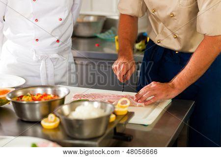 Close up von Köchen in einem Handels-Restaurant oder Hotel Küche arbeiten, bereiten sie ein Fisch Fi