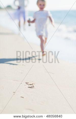 Closeup auf Sand und Mutter und Kind, die entlang der Küste