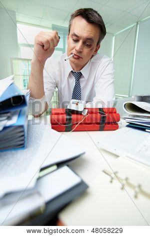 Experienced businessman with cigarette looking at dynamite